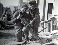 Jeune homme Français aide mitrailleur de la 70ème Division, 7e armée américaine, nettoyer son arme à Etzling, France. En date du 22 février 1945. Photo de Corps de signal.