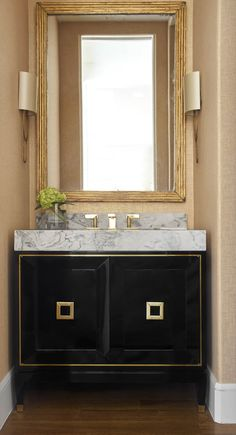 Beautiful powder room deisgn with black and gold vanity design and marble countertops | Jenkins Interiors