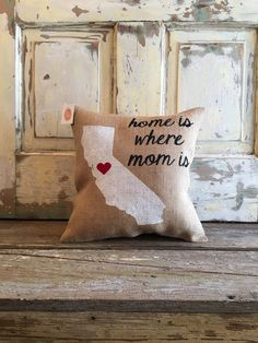 Melt moms heart with our best-selling Home is where Mom is pillow! Each burlap pillow is hand painted with a silhouette of your state and a