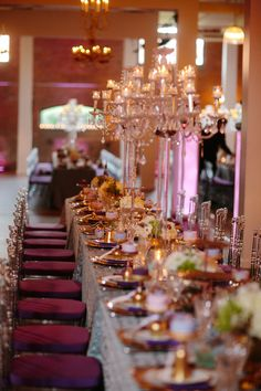 Purple and gold wedding table setting with crystal chandeliers