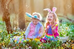 Kids on Easter egg hunt in blooming spring garden. Children with bunny ears searching for