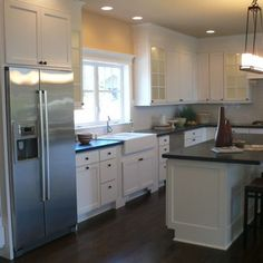 Dark wood floors, stainless appliance, white cabinets check.... Wall color and counter top not so sure
