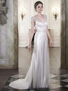 Maggie Sottero - ETTIA, The perfect blend of romance and refined sophistication is found in this tulle and Vogue satin sheath dress, complete with delicate tulle overlay, adorned with sparkling Swarovski crystals and pearl beads. Finished with ethereal tulle sleeves and covered button over zipper closure.