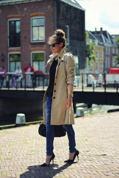 (Taking this look apart is so easy--trench, jeans, black tee, black heels, topknot, sunglasses--but she makes it look so chic.) trench