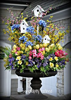 Spring urn planter flower arrangement with forsythia tulips daffodils and white bird houses.