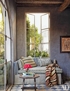 At the Malibu beachfront retreat of designer and antiques dealer Richard Shapiro, a daybed covered in stylishly mismatched stripes is tucked into a corner of the library; the table is 15th-century Italian, and the painting is by Shapiro.
