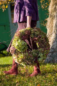 Sarah Raven walking with hydrangea wreath