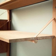 - very nice stuff - share it - very easy to replicate high-end look for a simple shelf. Just vertical members bolted into the wall and some shelves held by leather straps and rods. Very clever and definitely high-end looking.