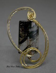 Lovely transparent and brown glass bead with gold plated wire wrap.