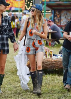 Cressida Bonas is wearing a pin-stripe matching set with black Hunter Wellies and a blue cap.