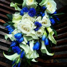 Brides tied shower bouquet of Calla Lilies, White Roses, Gentian and Cornflowers