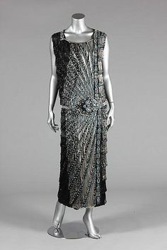A good beaded flapper dress, circa the black chiffon ground adorned with an embroidered belt in silver and turquoise beads, silver looped swags cascade in bands down one side, black looped fringes cover the remainder of the ground, ankle length Vintage Outfits, 1920s Outfits, Vintage Gowns, Vintage Mode, Silver Vintage Dresses, Vintage Clothing, 20s Fashion, Art Deco Fashion, Fashion History