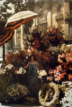 A woman stands in front of her flower stand on the Rambla in Barcelona, Spain, March 1929.Photograph by Jules Gervais Courtellemont, National Geographic