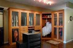 Luxury Closets - Light finish with spiral rod and glass-front cabinets. From The Closet Doctor http://www.closet-doctor.com/closets/luxury/closet-organizer-gallery