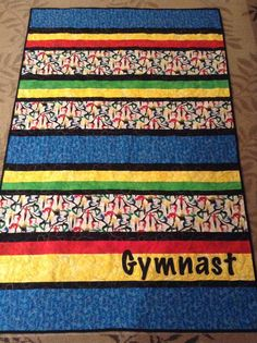 Gymnastics quilt for our gym fundraiser.  Simple stripes using gymnastics print fabric - ok for girls or boys.  Free motion quilted bubbles & loops.  Gymnast applique.  Back is soft green minky.  By Dawn