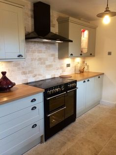 Howdens burford grey kitchen with tumbled marble tiles and cast iron handles