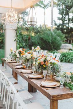 O vestido de noiva feito em renda tinha desenho de flores nas cores laranja e amarelo, mesma cor da decoração do casamento.