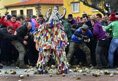 People throw turnips at a man representing the Jarrampla, beating his drum and sporting a costume covered in multicoloured ribbons and his face hidden behind a conical mask with a huge nose, horns and a horse's mane, in Piorna on January 19, 2017 during the annual San Sebastian festivities