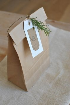 brown paper bag with twine tied rosemary sprig label   -  simply factory