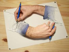 Optical Illusion of a man's hands drawing a picture.