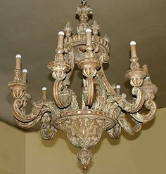 Italian, Baroque style, painted pine, ten-light Chandelier: With circular corona having urn-form finials supporting a tapering round tier cresting in leafage carved scrolling candle arms.  19th century.