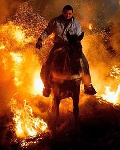 SAN BARTOLOME DE PINARES, SPAIN - JANUARY 16:  A man rides a horse through a bonfire during 'Las Luminarias' Festival on January 16, 2015 in San Bartolome de Pinares, Spain. In honor of Saint Antony the Abbot, the patron saint of animals, horses are riden through the bonfires on the night before the official day of honoring animals in Spain. The tradition which is hundreds of years old is meant to purify and protect the animal along the year.  (Photo by Pablo Blazquez Dominguez/Getty Images)