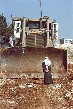 Palestinian man attempts to block a bulldozer from destroying his vineyard.
