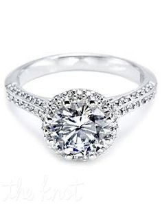 Platinum and diamond solitaire Engagement Ring, pictured with a round brilliant-cut center stone held in place with eight prongs. There are round pave-set diamonds around the center stone and on the shoulders of the ring. Variations on this setting include either hand-engraving or a smooth high-polish finish on the the band, as well as Petite and Medium proportions.