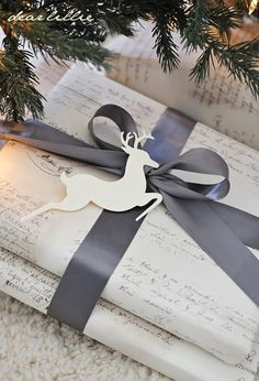 Gift wrapped in script paper with grey satin ribbon and reindeer ornament