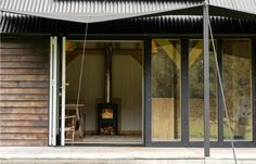 shade device, outdoor tension structure  :::  The deck has a canvas shade stitched by a sailmaker and a corrugated black metal roof (see more on metal roofs here). The cabin is heated by woodstove and has solar-powered lighting. Exterior cladding Shou Sugi Ban sorched timber | Rupert McKelvie, Devon
