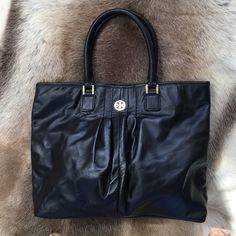 "Tory Burch - Black leather tote Buttery, black leather with pleating. Gold hardware. Used only a handful of times. Purchased from Tory Burch store in Ala Moana, HI. Excellent, used condition. Small spot, less than inch diameter in main interior, inner button has minor wear from keeping bag closed at top, interior pocket has small spots. Original dust bag included. 17""L x 12""W x 3""D. Tory Burch Bags Totes"