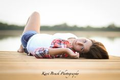 2015 High School Senior girl for posing picture ideas. Senior girl laying on a dock by a lake at sunset. High school senior session pose inspiration for senior pictures. Kari Bruck Photography