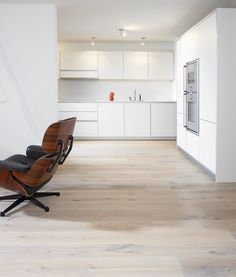 Country Oak wide plank flooring complements the handleless white contemporary kitchen units