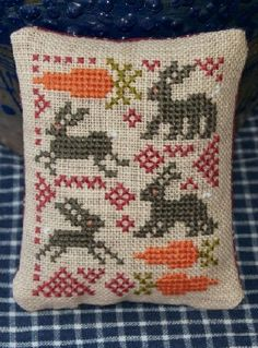 Cross stitch Easter mini pillow or pin keep with rabbits and carrots.  Design by Kathy Barrick.