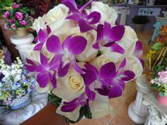 Bridal bouquet of Ivory Roses and purple Dendrobium Orchids. Designed by China Rose Florist,  Marco Island, Fl.