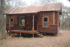 "Tiny Texas Houses: Koehler ""Cowboy Cottage"" - Exterior. This 12'x28' energy-efficient cottage is built w/salvage materials. It has a full kitchen, full bath with cast-iron claw-foot tub & 2 sleeping lofts, plus a downstairs sleeping nook. It has 2, 6'x12' porches, the back is screened-in. 3of3."