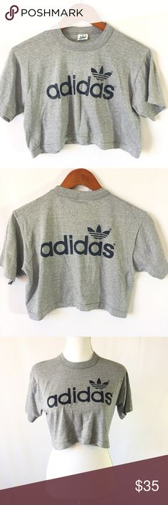 Adidas Original Trefoil Spell Out Logo Crop Top Trefoil logo Adidas Original gray crop top shirt. RARE Spell out and logo on front AND back of top. Excellent Used Condition. Small flaw on the S (on front), otherwise No other obvious marks, defects or flaws. 50% cotton, 50% Polyester.  Measurements - In inches, taken flat and are approximate (double where appropriate): 19.5 bust, 16 length. adidas Tops Crop Tops