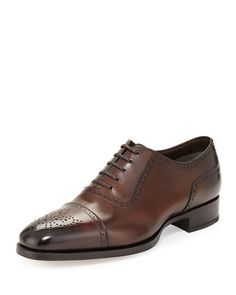 """Tom Ford calfskin oxford shoe with brogue detailing. 1.3"""" stacked heel. Medallion cap toe. Lace-up front. Leather lining and insole. Leather/rubber sole. """"Austin"""" is made in Italy."""