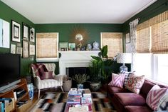 Living room- The sunburst mirror provides a good focal point for the room. Putting a gallery wall around the TV helped  it to not stand out quite so much. The sofa and tables are all vintage. Design*Sponge Sneak Peek