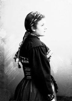 Studioportrett av kvinne i drakt og bånd i håret. Avfotografert fra siden. - Norsk Folkemuseum / DigitaltMuseum | Raudtrøye
