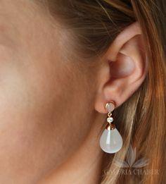 Klasyczne, długie kolczyki wykonane ze srebra próby 925, w kolorze złotym. W wyrobie osadzono przepiekny kamień o barwie mleczno-perłowej oraz jego mniejszą wersję o barwie jasno-różowej przy zapięciu. Dodatkowo kolczyki ozdobiono klasycznymi cyrkoniami w kolorze białym. Zapięcie na sztyft. Cały kolczyk o długości około 3,5 cm.