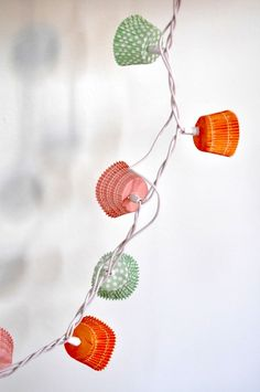 Cupcake Liner String of Lights -Decorate a string of lights by punching a hole through the center of each liner - then push the light through.  Get the instructions at Caitlin Wilson Design