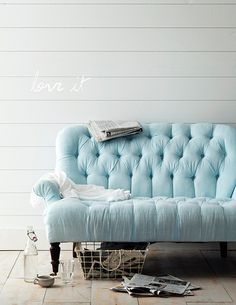 pale blue sofa and white walls, floorboards,  I can't speak