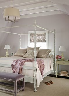 Elegant bedroom features vaulted ceiling lined with white beams over lavender painted walls framing a gray canopy bed dressed in taupe bedding and purple silk throw situated under small window dressed in purple print roman shade flanked by gray nightstands topped with gray gourd lamps alongside a purple velvet bench with silver nailhead trim placed at the foot of the bed illuminated by a Six Light Square Tube Chandelier.