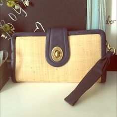 """COACH • Natural Straw& Leather Clutch Natural Straw& Leather Clutch has a blonde, natural straw body with navy blue leather trim and brass-tone buckle – Detachable 6 ½""""L wristlet – Zipper closure top with open interior – Model number marked inside """"L0868-4274"""" Like new- a small scratch in the back Coach Bags Clutches & Wristlets"""