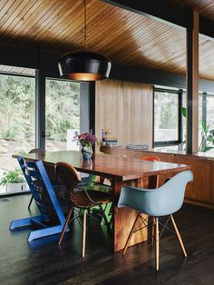 An assortment of dining chairs, including vintage iterations on the Eames shell chair by Charles and Ray Eames and Stokke's Tripp Trapp chair, are clustered around a table in this midcentury Portland home.
