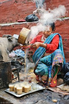 Old lady filling tea glass, a rural age time in ancient Nepal
