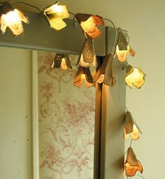 To spruce up a string of 'fairy lights', all you really need is a cardboard egg carton and some scissors. Esprit Cabane created this lovely set of flower-shaped light covers which, when trimmed and fitted over the lights, give a warm, cozy effect. Use LED lights only to prevent this pretty DIY light project from turning into a fire hazard
