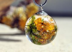 Resin necklace with yellow flower forest, natural moss, tree bark.  All of my jewelry is created in my home studio.   Making my adornments I use only natural materials: routs of plants, flowers, leaves, elements of trees, moss, natural coloring matter etc.   I create adornments for women that love natural style.  Adornments of plants keep natures soul and underline womens tiffany natures.  All of the adornments are created in a positive soul move.   Material: eco resin, yellow flower…