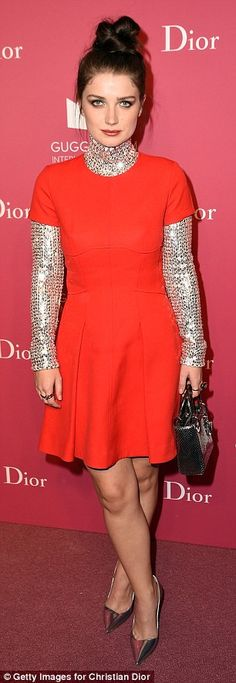 Glam look: Eve Hewson donned an orange skater dress worn over a sequinned top...